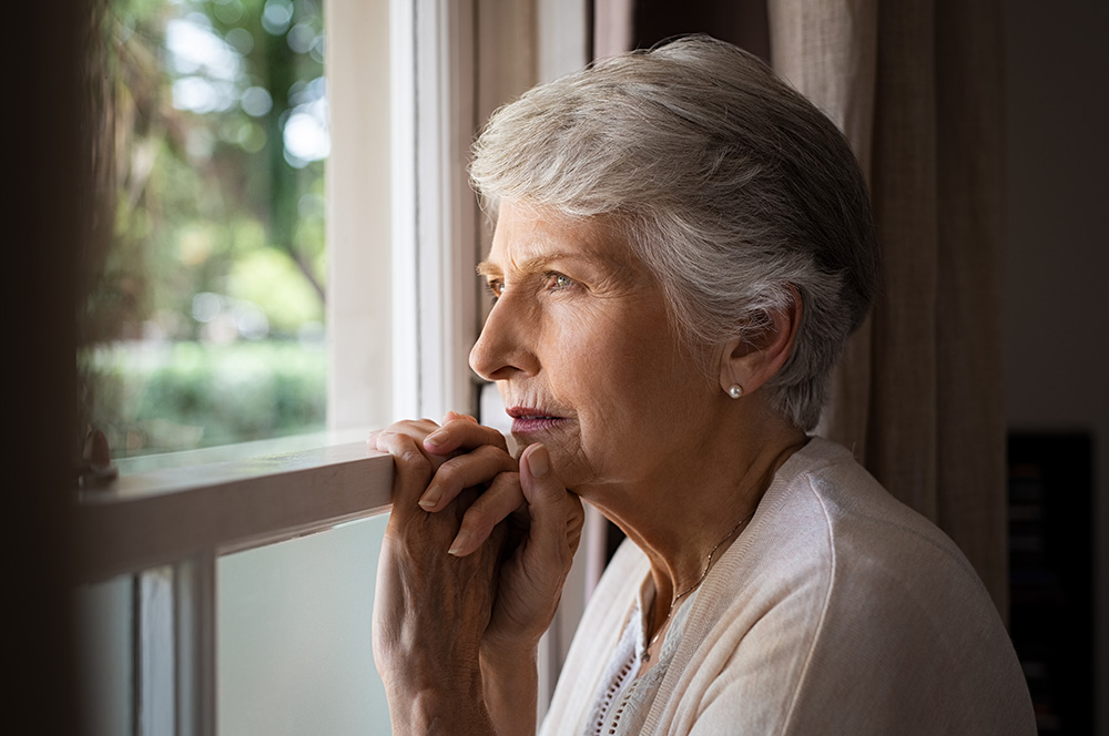 Grieving woman looking out window