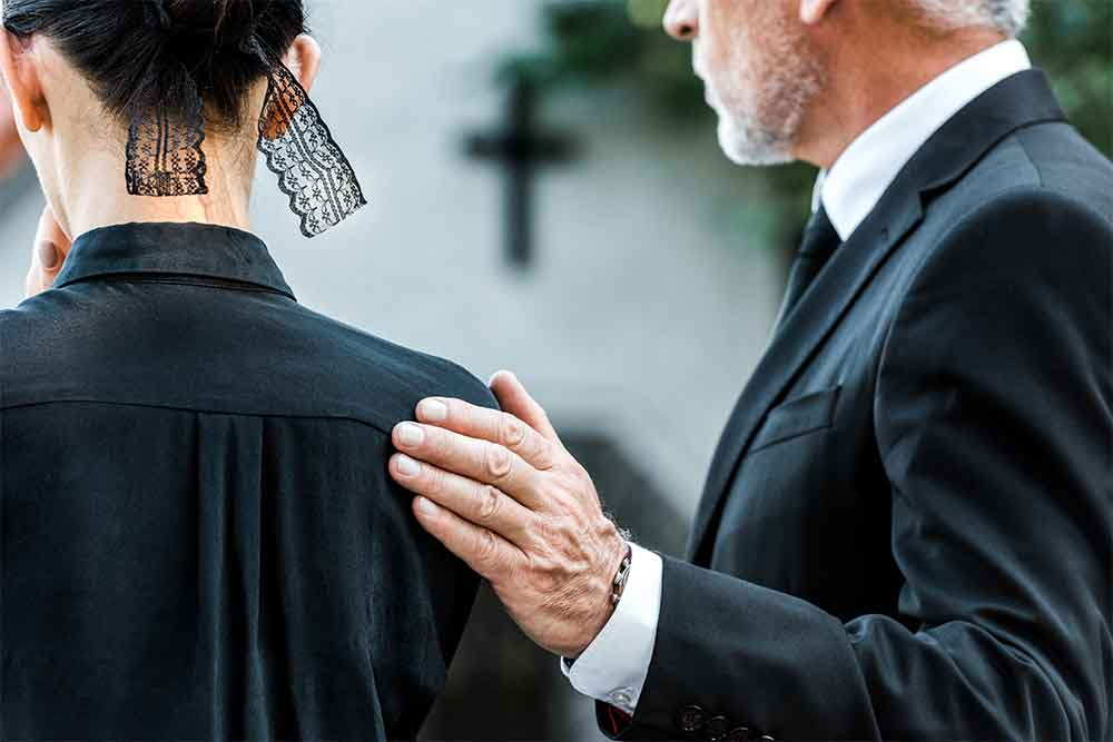 Gentleman comforting woman at a funeral