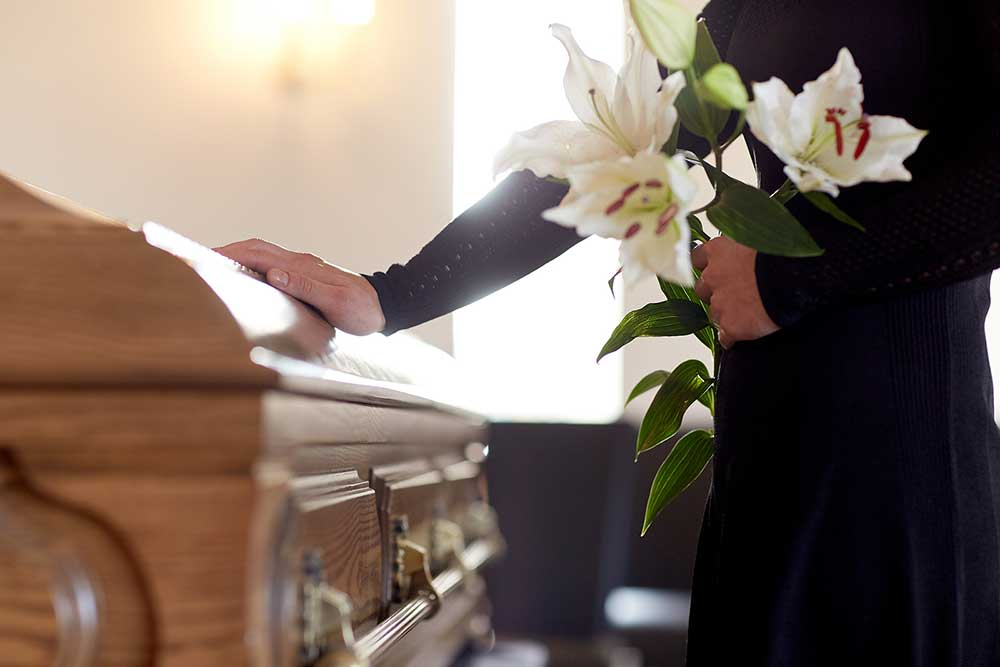 Woman touching a closed casket with a bouquet of lilies in hand